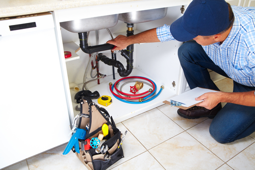 Technician fixing kitchen sink plumbing