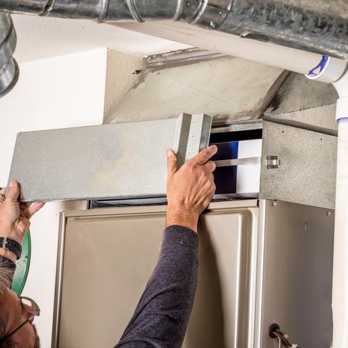 Technician replacing HVAC unit filter